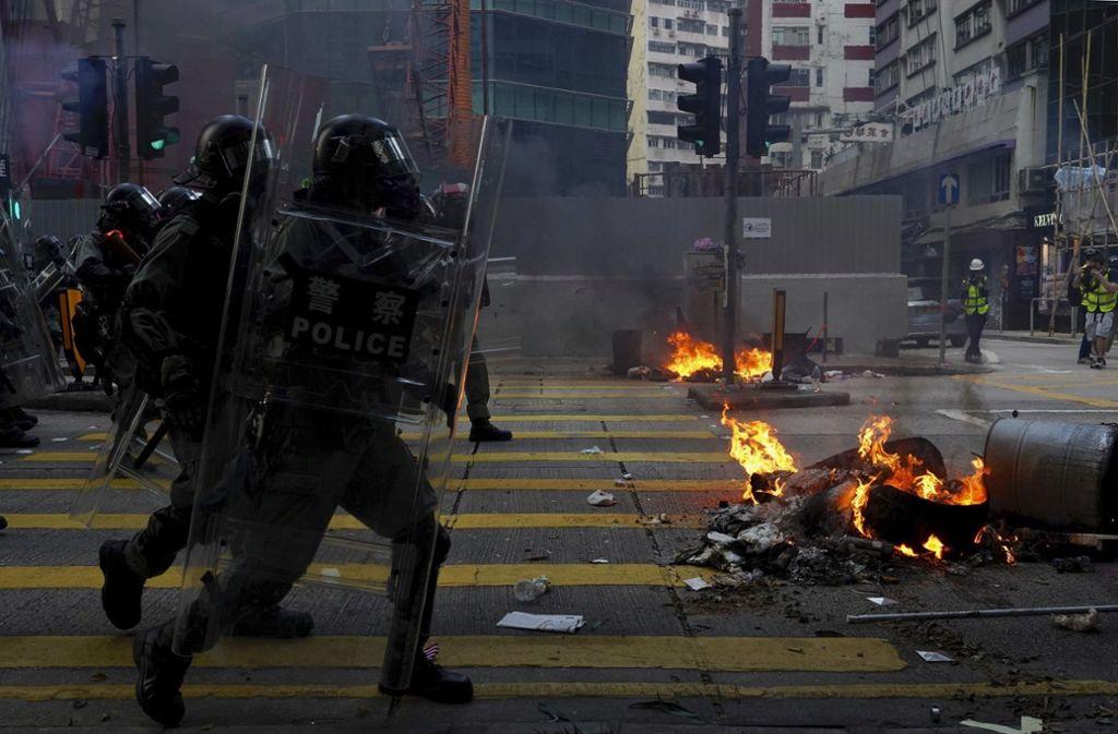 Polizisten in Schutzkleidung laufen während einer Demonstration in Hongkong  nahe einer brennenden Barrikade. Foto: dpa/Vincent Yu