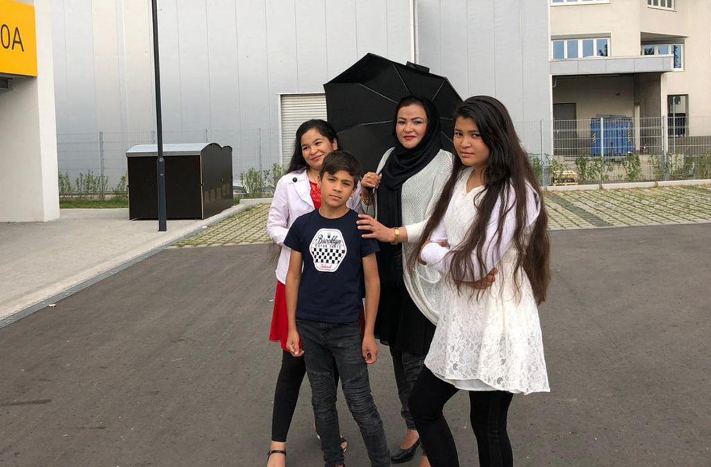 Sakina Esmaily und ihre drei Kinder Mohadesha (li.), Mortaza (2.v.li.) und Mahdia (re.) vor ihrem derzeitigen Zuhause. Foto: Esmaily