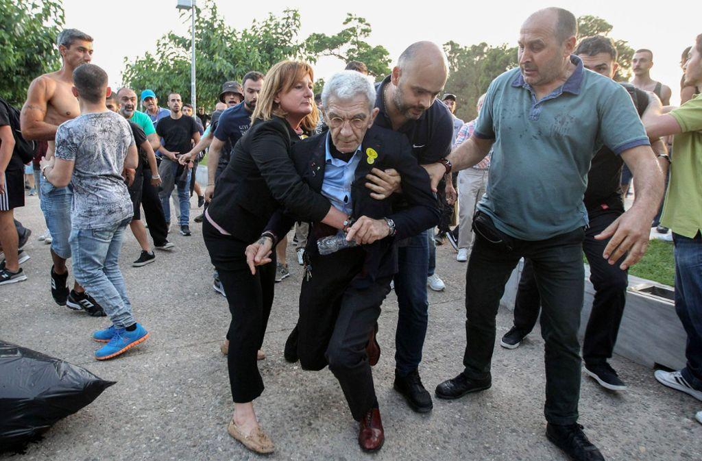Bürgermeister Yiannis Boutaris muss nach dem Angriff gestützt werden. Foto: Eurokinissi