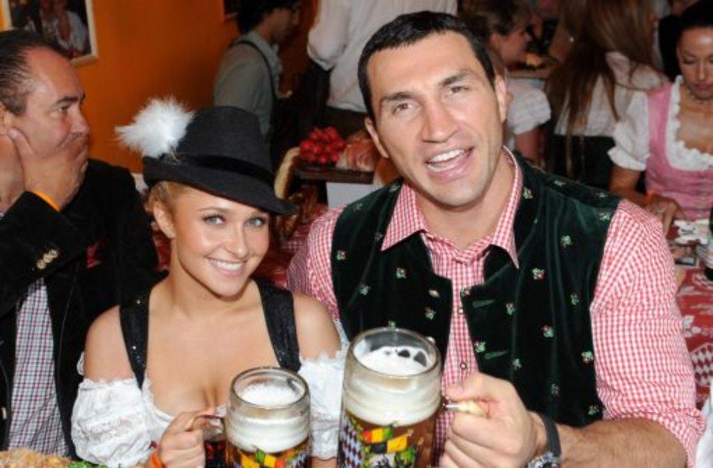 So sah man ihn selten: Der Profiboxer Wladimir Klitschko auf dem Münchner Oktoberfest in rot-weiß-kariertem Hemd und passender dunkelgrüner Weste. Neben ihm Hayden Panettiere mit einem forstgrünen Jägerhut. Foto: dpa