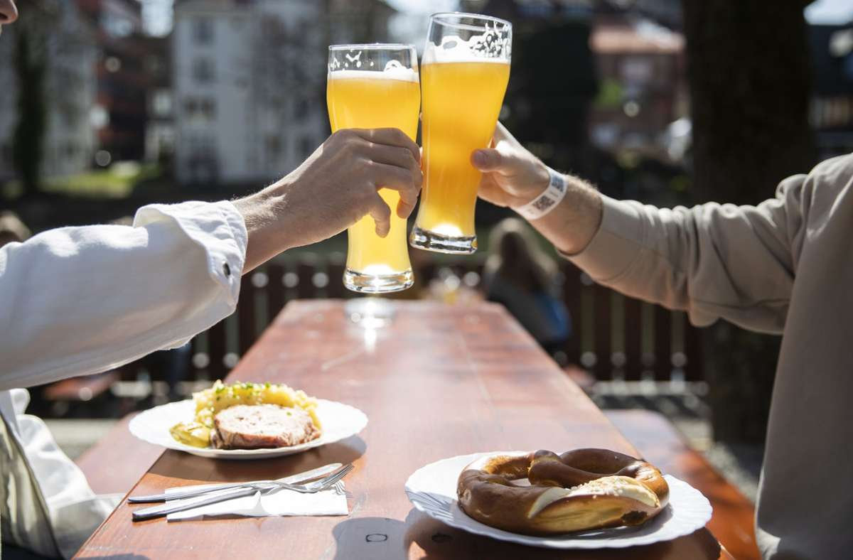 Tübingen: Zwei Menschen sitzen bei gutem Wetter in einem Biergarten und stoßen mit einem Bier an. In Tübingen können Menschen in der Stadt kostenlose Corona-Tests machen. Foto: dpa/Tom Weller