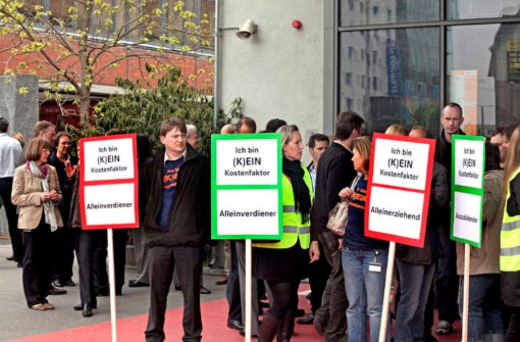 Hoffnungslosigkeit und Trauer: ein Mercedes-Benz-Bank-Mitarbeiter protestieren vor dem Stuttgarter Theaterhaus gegen die Verlagerung und den Abbau von Stellen. Foto: Rudel