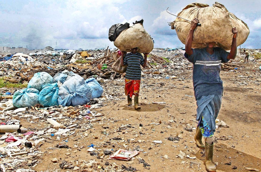 Ein Bild der Armut von der Elfenbeinküste: Frauen tragen in Abidjan recyclingfähige Materialien, die sie auf einer Deponie  gesammelt haben. Foto: dpa