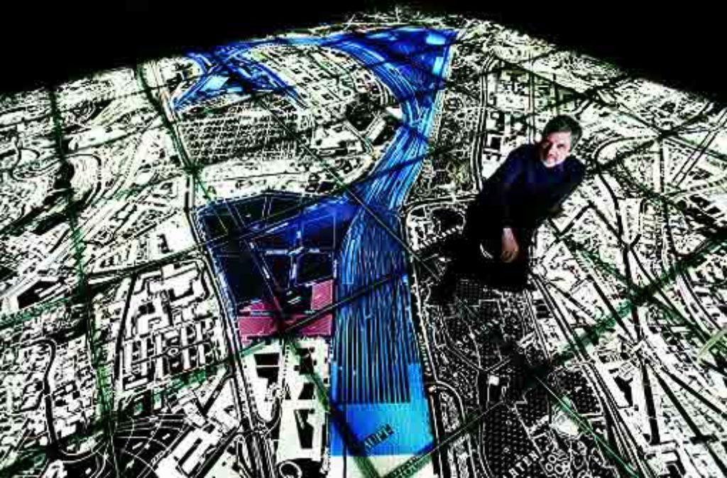 Ortwin Renn sitzt auf dem Modell von Stuttgart 21, das im Bahnhofsturm zu sehen ist. Er sagt, dass wir den Frieden in die Stadt zurückbringen müssen. Foto: Heiss