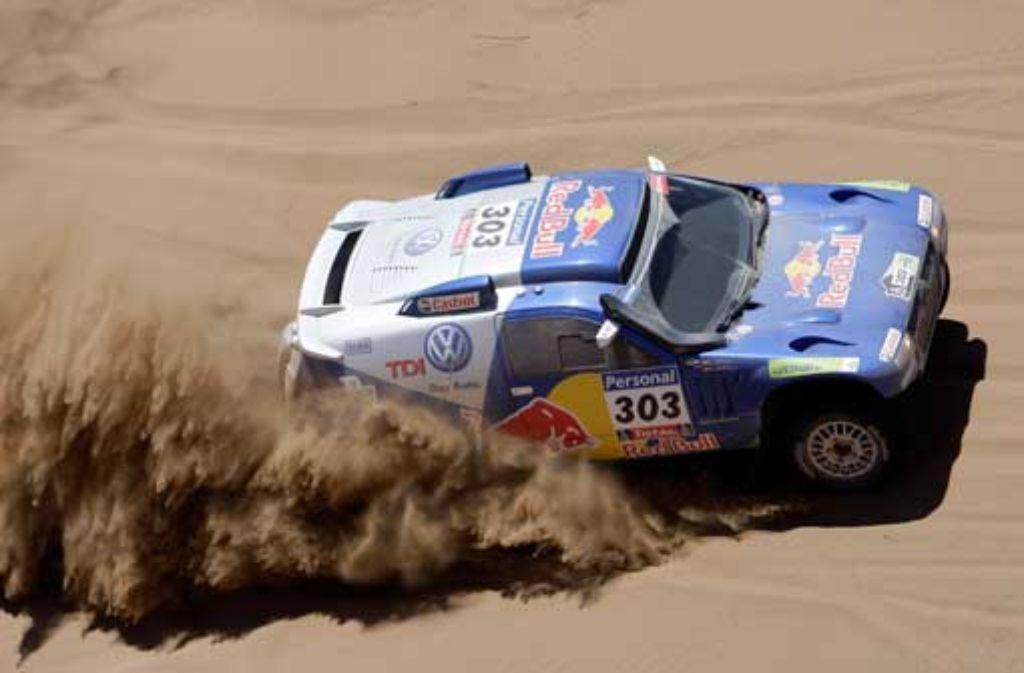 Carlos Sainz steuert sein Fahrzeug über einen Sandhügel. Foto: AP