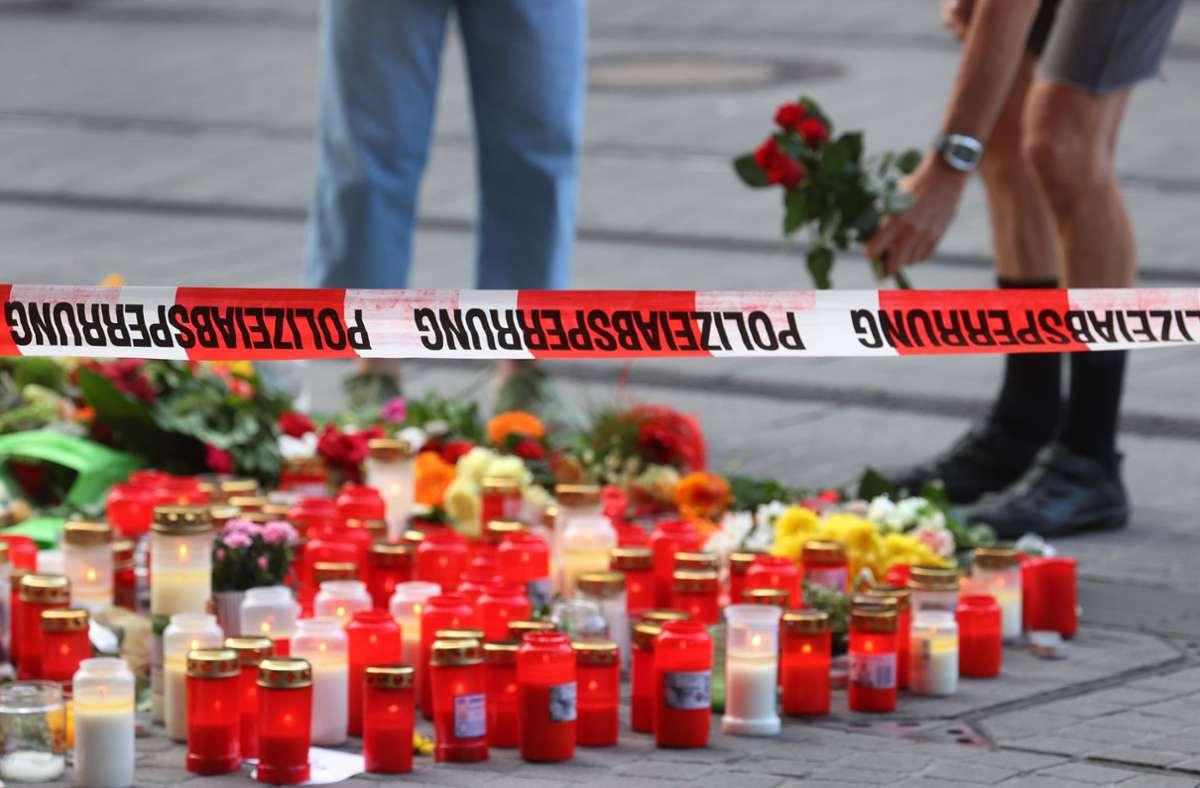 Blumen werden in Würzburg vor einem abgesperrten Kaufhaus, dem Ort des Anschlags, niedergelegt. Foto: dpa/Karl-Josef Hildenbrand