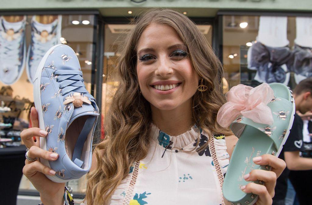 Werbeträgerin im Wortsinne: Cathy Hummels hält während einer Präsentation zwei Exemplare ihrer Schuh-Kollektion vor. Foto: dpa