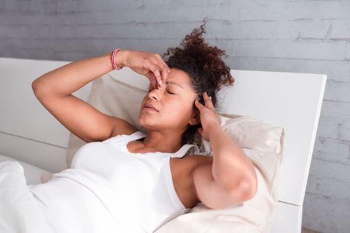 Frau im Bett mit Exploding Head Syndrome