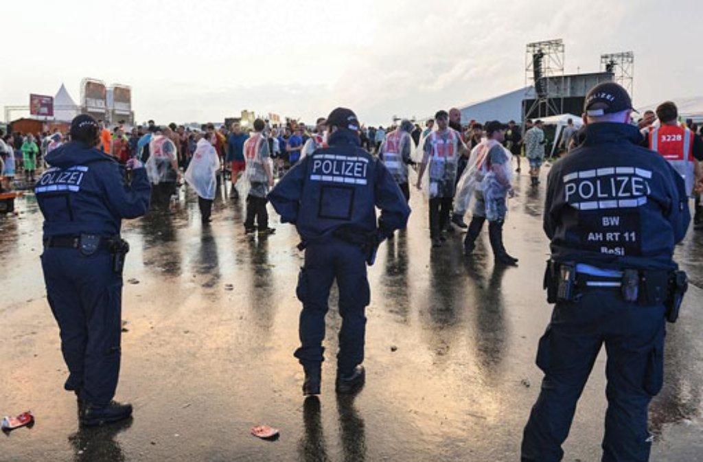Polizisten nach einer Unwetterwarnung im Regen das Festivalgelände ab. Foto: dpa