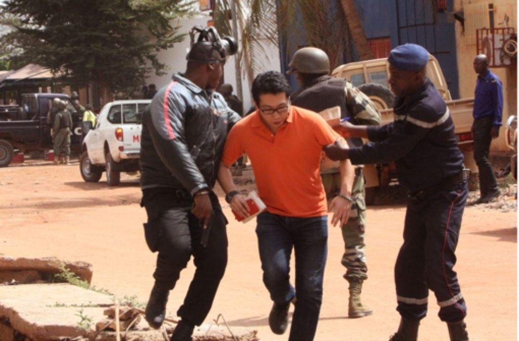Malische Soldaten bringen einen Mann in Sicherheit, der vor den Geiselnehmern im Mali Radisson Blu Hotel von Bamako flüchtet. Foto: AP