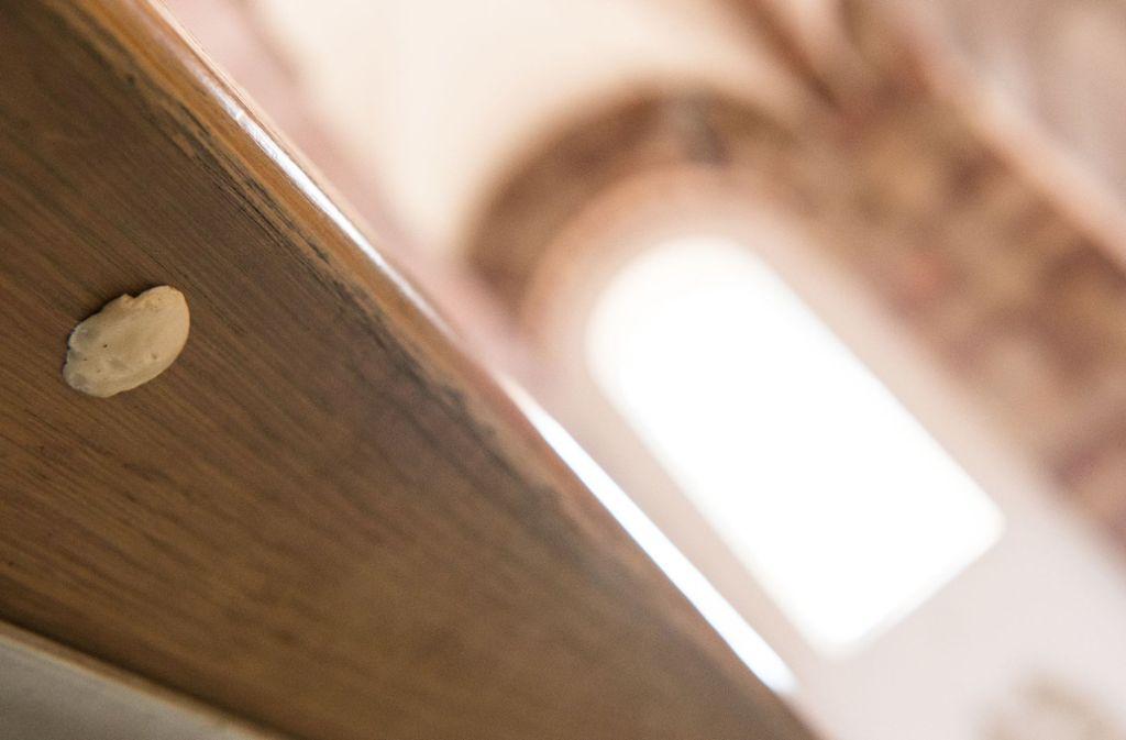 Ein Kaugummi klebt unter der Rückenlehne einer Sitzbank im Kaiser- und Mariendom zu Speyer. Die Dom-Mitarbeiter   müssen nach eigener Aussage sehr viel Aufwand betreiben, um Kaugummis die am Boden und unter den Sitzbänken kleben, wieder zu entfernen. Foto: Andreas Arnold/dpa