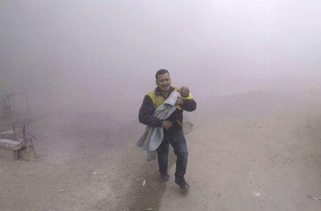 Dieses vom Syrischen Zivilschutz (Weißhelme) bereitgestellte Foto zeigt einen Notarzt, der seinen verletzten Sohn nach einem Luftangriff auf einen von Rebellen kontrollierten Vorort von Damaskus wegbringt. Foto: Syrian Civil Defense White Helme