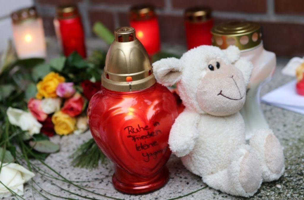 Rosen, Kerzen und Kuscheltiere liegen zum Gedenken an die  dreijährige Yagmur vor einem Hauseingang im Stadtteil Billstedt in Hamburg. Foto: dpa