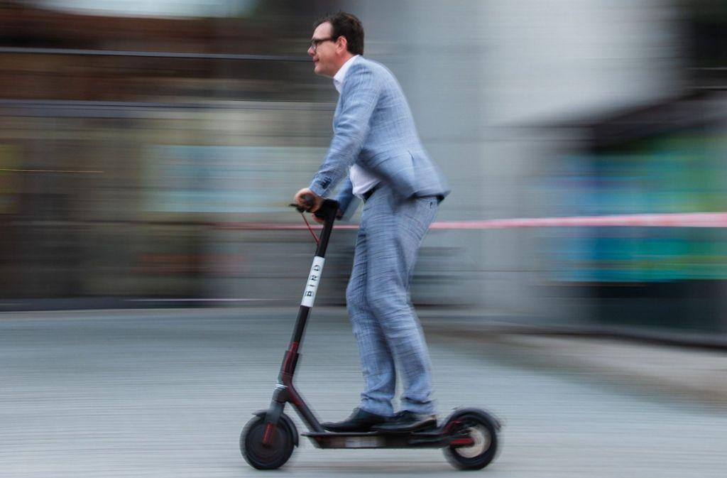 """Der Pressesprecher der Stadtwerke Bamberg, Jan Giersberg, fährt mit einem Elektro-Scooter des US-amerikanischen E-Scooter-Sharing Anbieters """"Bird"""" durch das Zentrum der bayerischen Stadt. Foto: dpa"""