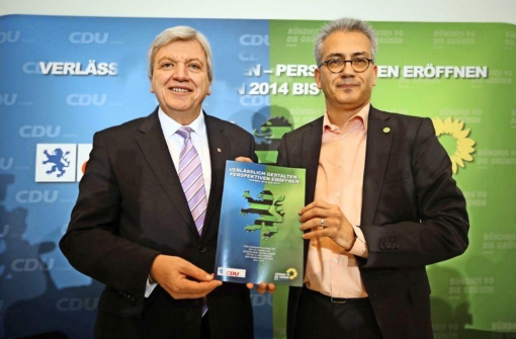 Volker Bouffier und Tarek Al-Wazir mit dem schwarz-grünen Koalitionsvertrag. Foto: dpa