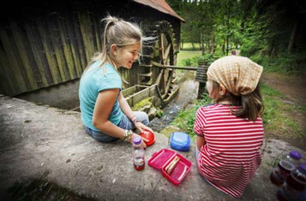 Lea (links) und Ina (rechts) stärken sich neben dem Mühlrad. Foto: Gottfried Stoppel