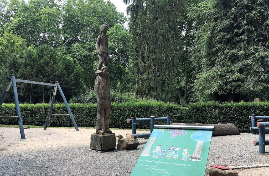 Ein Vater trägt seinen Sohn auf den Schultern – Holzskulptur im Karlsruher Trauergarten. Foto: /Frühauf