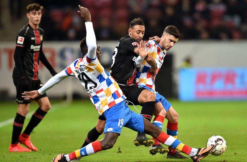 Die Mainzer Moussa Niakhate (l) und Aaron Martin (r) spielen gegen Leverkusens Karim Bellarabi. Foto: dpa