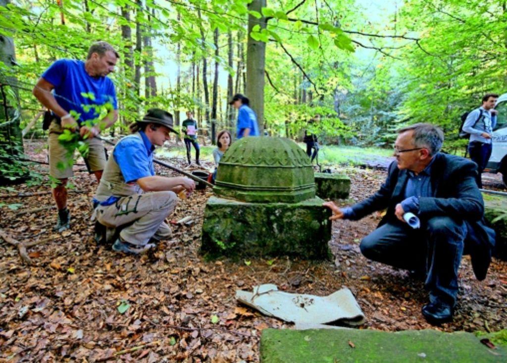 Der umgedrehte Stein war am Sockel festbetoniert – Pfarrer Eberhard Schwarz (re.) beobachtet die Bergung aufmerksam. Foto: factum/Weise