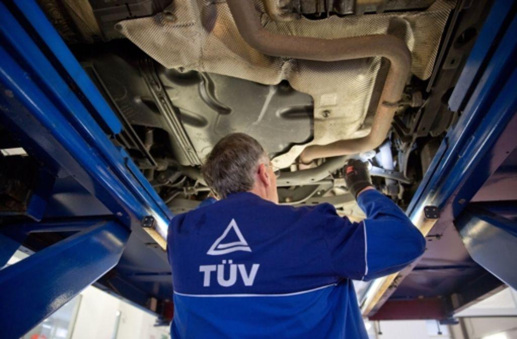 Tüv-Prüfer bei der Untersuchung eines Fahrzeugs. Foto: dpa