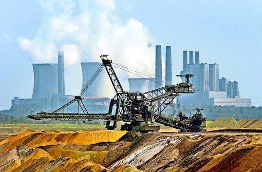 Ein Bagger vor der Kulisse des RWE-Kraftwerks Niederaußem in Nordrhein-Westfalen: die Braunkohle, die hier abgebaut und verfeuert wird, gilt als besonders klimaschädlich – ist jedoch für die Kraftwerksbetreiber immer noch ein sehr wirtschaftlicher Brennstoff. Foto: dpa