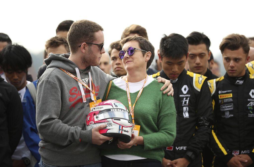 Der Bruder und die Mutter von Anthoine Hubert halten den Helm des verstorbenen Fahrers bei der Gedenkminute in Spa-Francorchamps Foto: AP