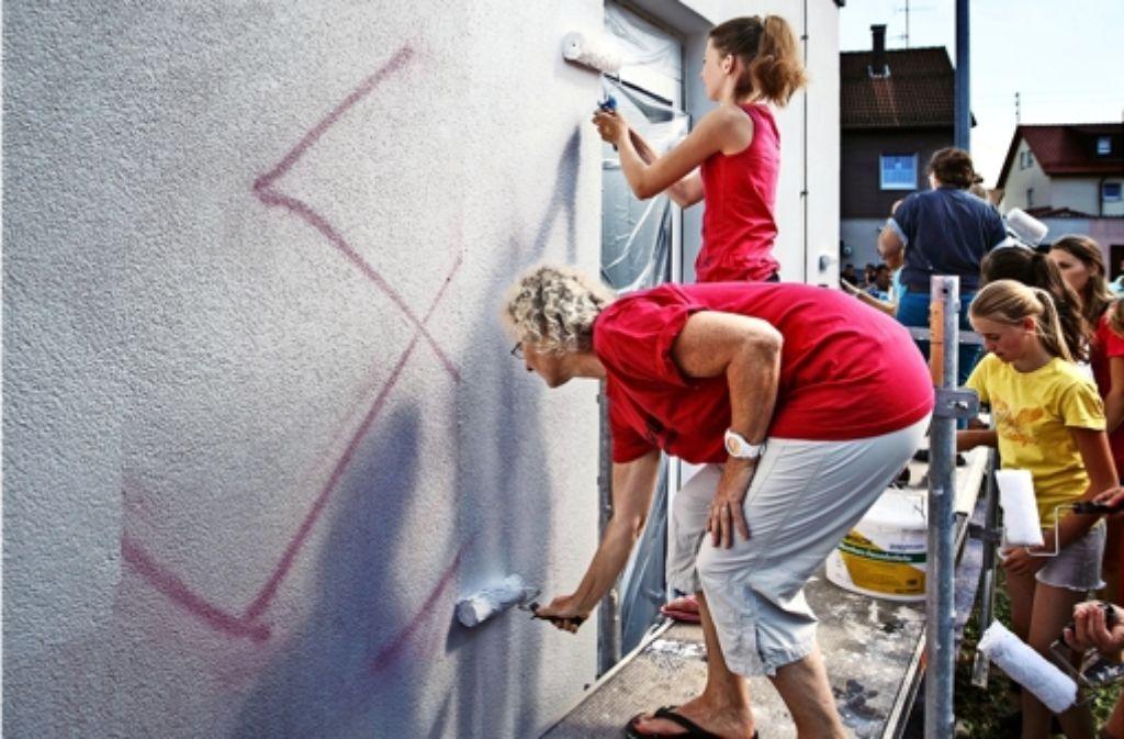 Die Helfer stehen Schlange, um die Hakenkreuze zu beseitigen. Foto: Gottfried Stoppel
