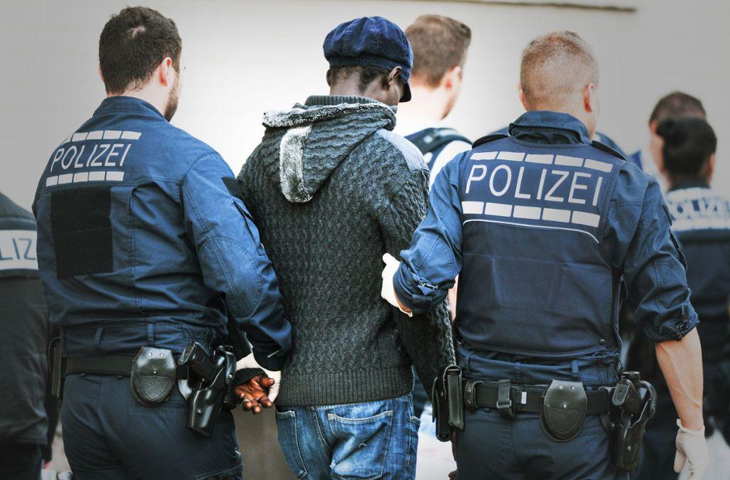 Polizisten führen bei einer Drogenrazzia 2015 in Mannheim vor der Landeserstaufnahmestelle für Flüchtlinge einen Verdächtigen ab. Foto: dpa, Lichtgut/Leif Piechowski