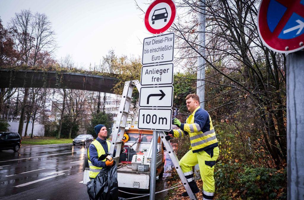 Von 1. Januar an dürfen hier  keine Euro-5-Diesel mehr rein:  Alex Naujocks (von links)  und mit  Ürkmez stellen die neuen Schilder an der Cannstatter Straße auf. Zunächst werden sie bis zum 1. noch abgedeckt. Foto: Lichtgut/Achim Zweygarth