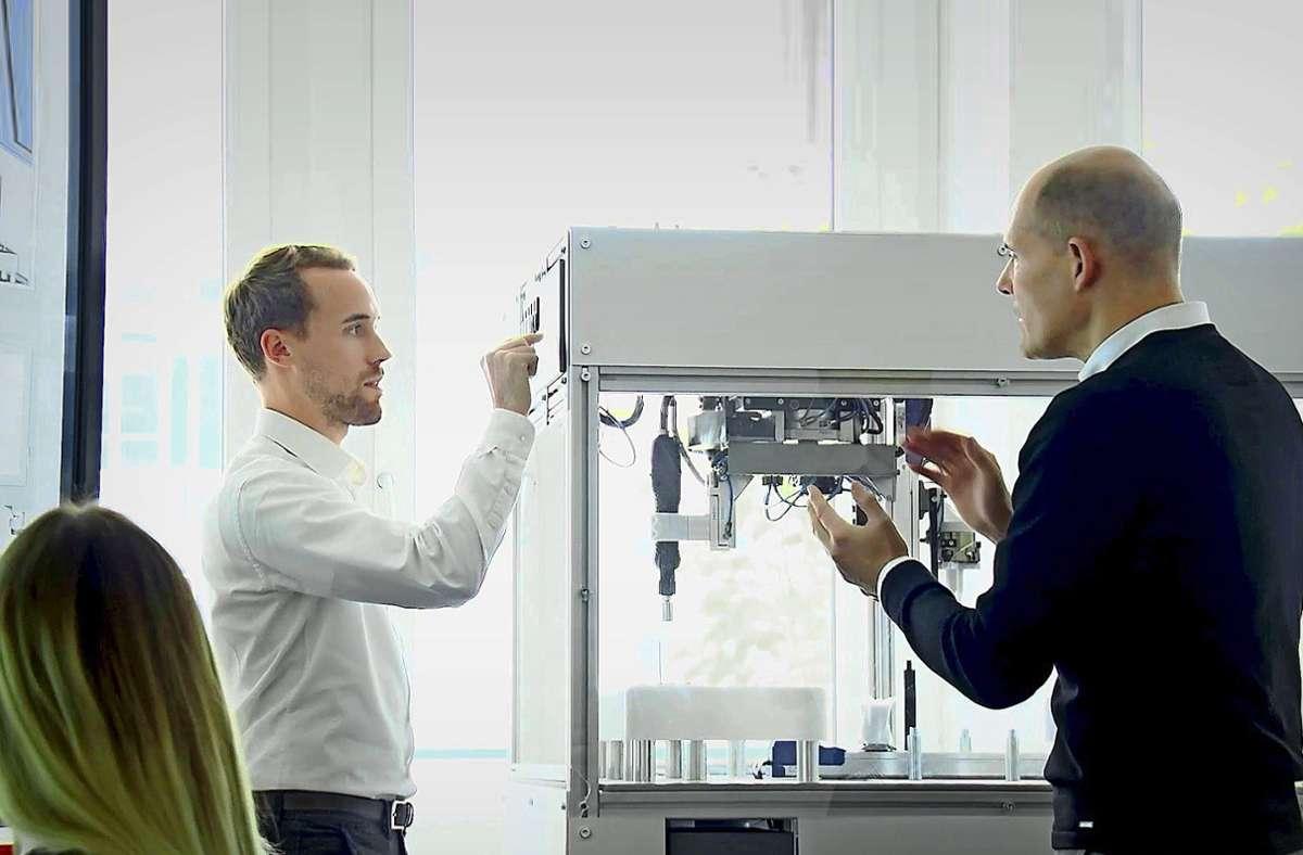 Mathias Stach  (rechts), der Sprecher der Geschäftsführung von Ascon Systems, prüft das Verhalten einer Anlage, die von einer speziellen App gesteuert wird. Foto: Ascon Systems