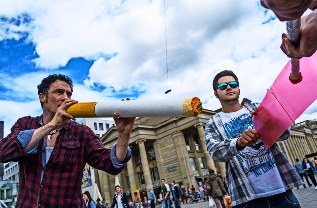 Mit übergroßen Zigaretten und Streichhölzern   macht eine Theatergruppe auf den  Nichtrauchertag aufmerksam. Foto: Lichtgut/Max Kovalenko