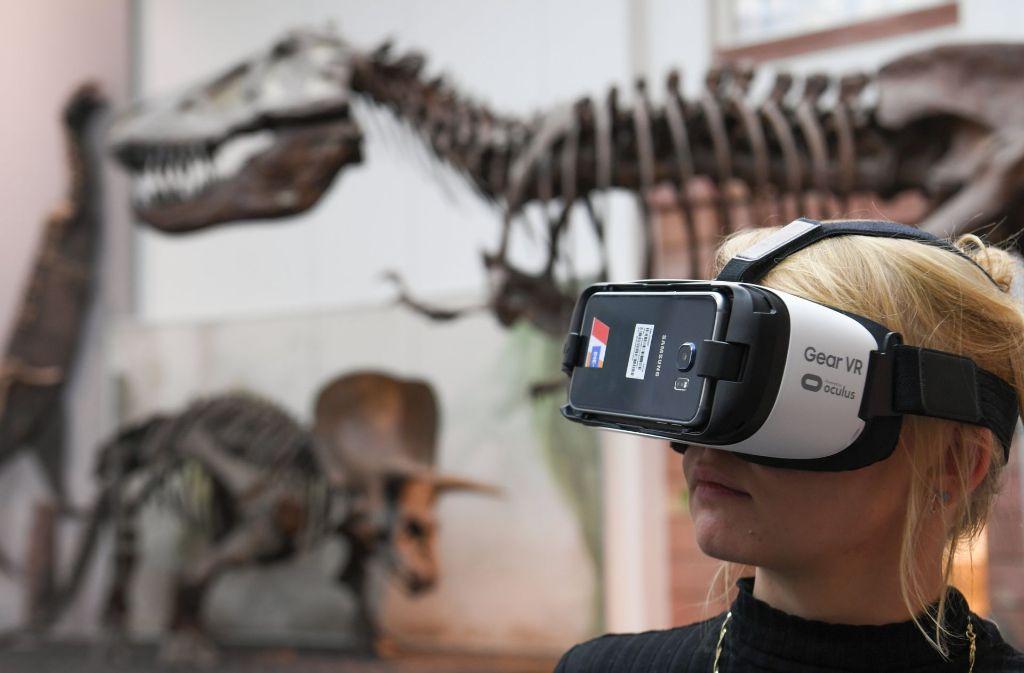 Ein junges Mädchen steht mit einer Virtual-Reality-Brille im Naturmuseum Senckenberg in Frankfurt am Main (Hessen) im Sauriersaal. Mit Virtual-Reality-Anwendungen lässt das Museum ausgestorbene Saurier zu neuem Leben erwachen. Per Datenbrille können Besucher in die Urzeit eintauchen. Foto: dpa
