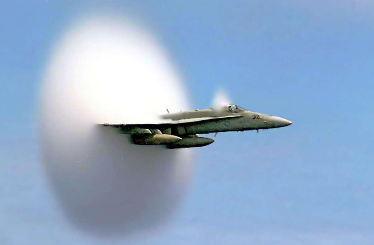 Ein Jagdbomber vom Typ F/A-18 Hornet der US-Navy beim Durchbrechen der Schallmauere:  Man sieht den Wolkenscheibeneffekt. Die Schallgeschwindigkeit in trockener Luft von 20 Grad Celsius  343,2 Meter pro Sekunde (m/s) – also 1236 Kilometer pro Stunde (km/h). Foto: Wikipedia commons/Ensign John Gay, U.S. Navy