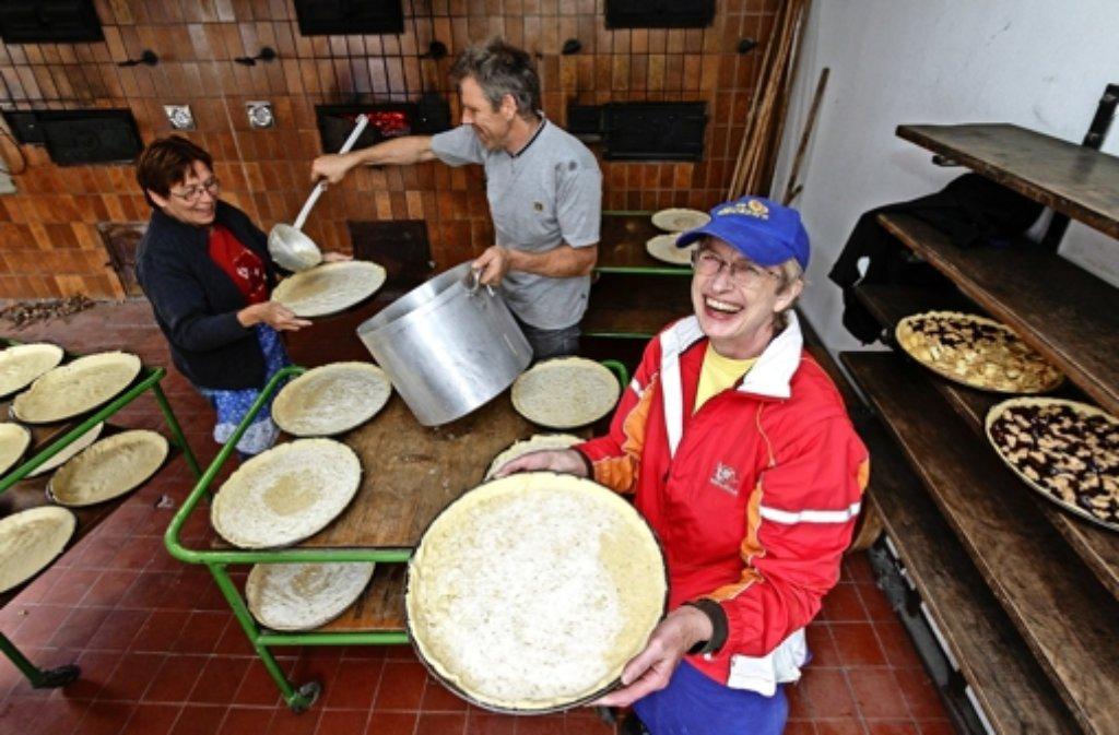 Im Backhaus werden Zwiebelkuchen für das Straßenfest gebacken.   Ulrike Wörner (mit Mütze), Gerda Ziegler und  Frank Werner zeigen, wie Teamwork geht. Foto: factum/Bach