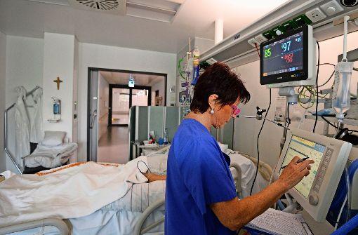 Eine Krankenschwester betreut im St. Josefskrankenhaus in Freiburg  auf der Intensivstation einen Patienten. Foto: dpa