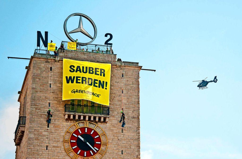 Greenpeace-Aktivisten haben am Freitag ein Banner auf dem Bahnhofsturm angebracht. Sie fordern bessere Luft. Foto: dpa