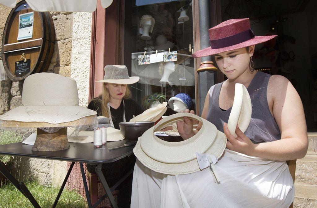 Franziska Lambart (rechts) und  Birgit Sophie Metzger nähen bei gutem Wetter ihre Hüte auch mal vor dem Haus in der Webergasse 7 in Esslingen. Foto: