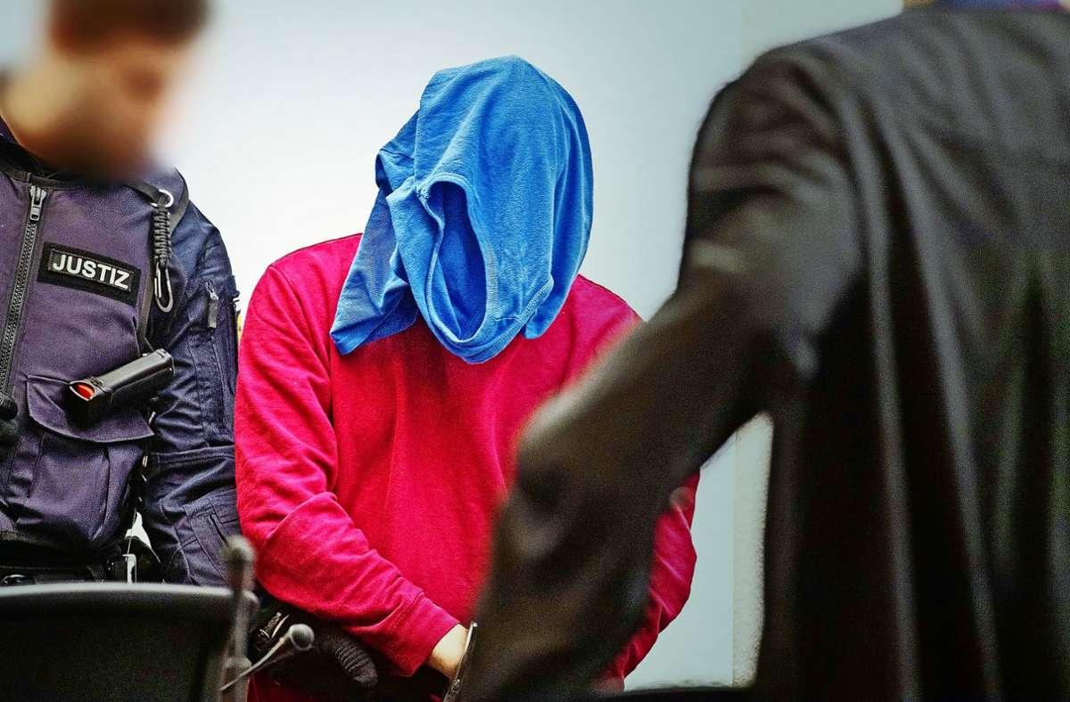 Der Angeklagte verbirgt sein Gesicht – und schweigt weiterhin. Foto: dpa/Marijan Murat