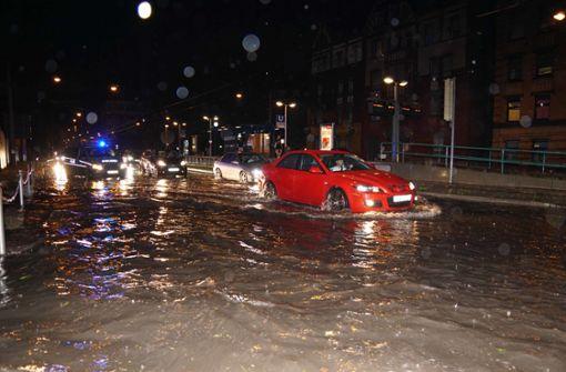 Autos kämpfen sich durch Wassermassen auf der Straße