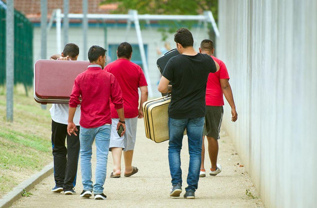 Flüchtlinge laufen mit Koffern bepackt auf einem Weg einer Erstaufnahmeeinrichtung im Jahr 2015. Foto: dpa