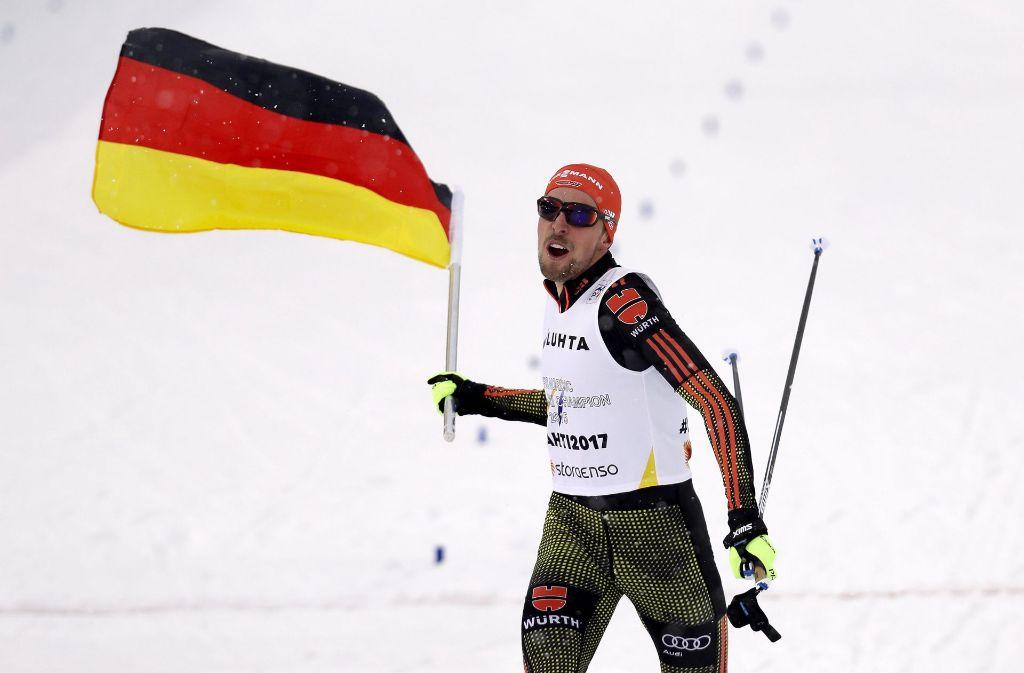 Eric Frenzel schwingt die deutsche Fahne nach dem Gold-Triumph im Teamwettbewerb. Foto: AP
