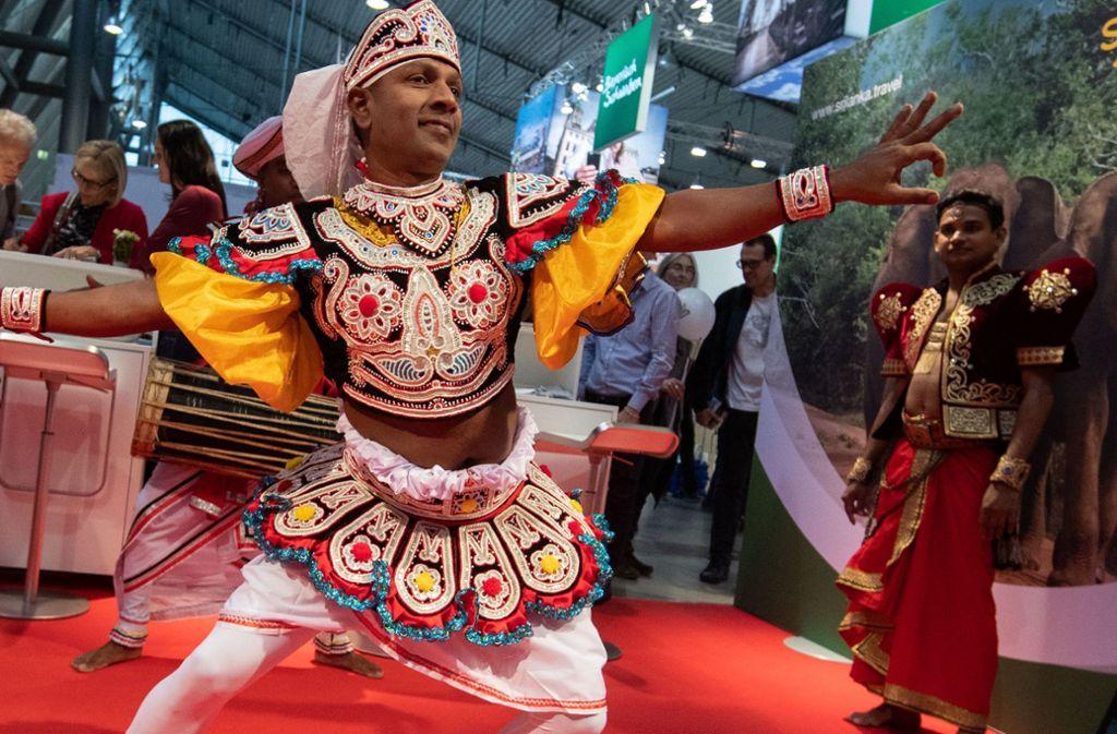 Ein Mann in traditioneller Kleidung tanzt am Stand von Sri Lanka auf der Reisemesse CMT Foto: dpa/Marijan Murat