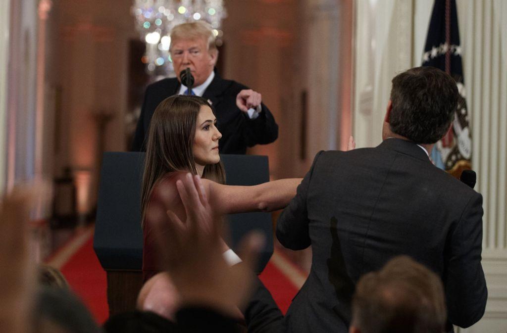 Präsident Donald Trump fixiert den CNN-Journalisten Jim Acosta, während eine Mitarbeiterin dem Journalisten das Mikrofon wegnimmt. Foto: AP