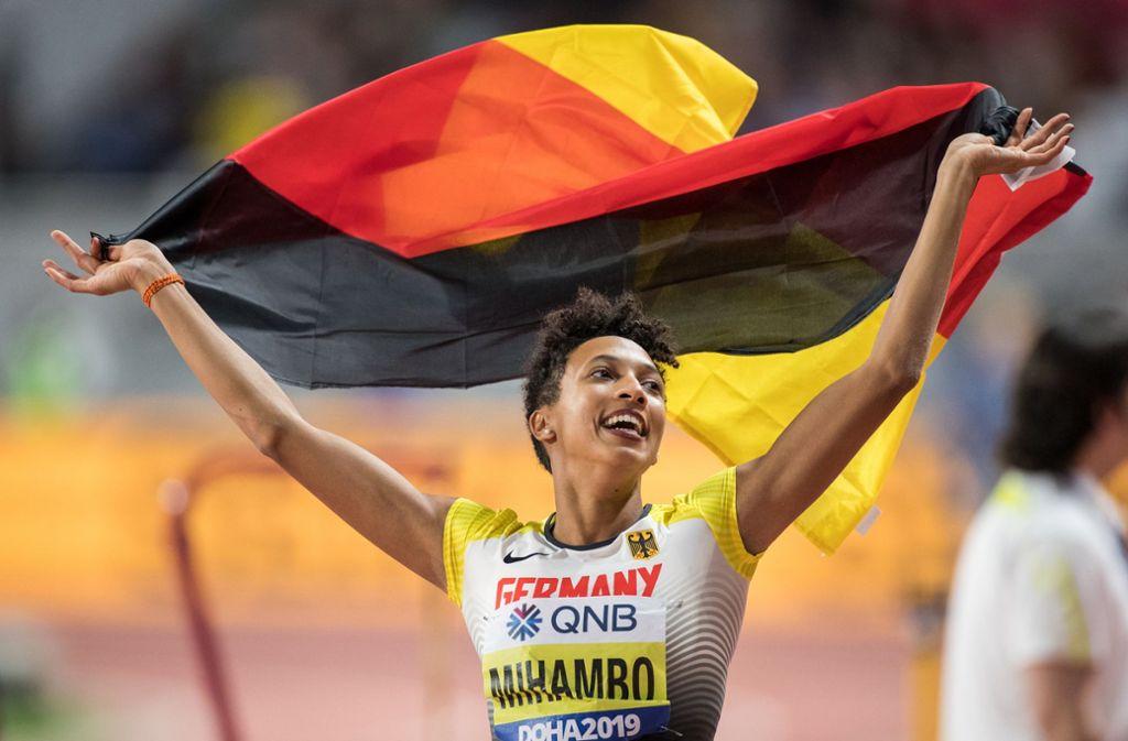 Malaika Mihambo aus Deutschland jubelt mit einer deutschen Fahne über ihren Sieg bei der WM in Doha. Foto: dpa/Oliver Weiken