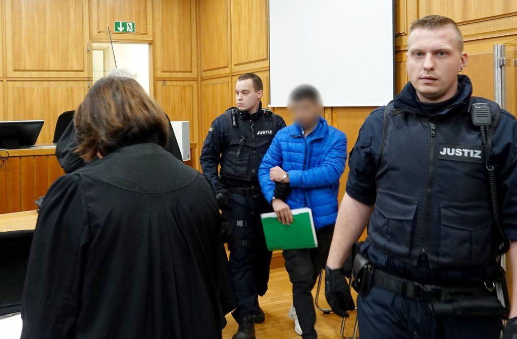 Einer der drei beschuldigten Männer wird von Justizbeamten in den Gerichtssaal geführt. Foto: dpa