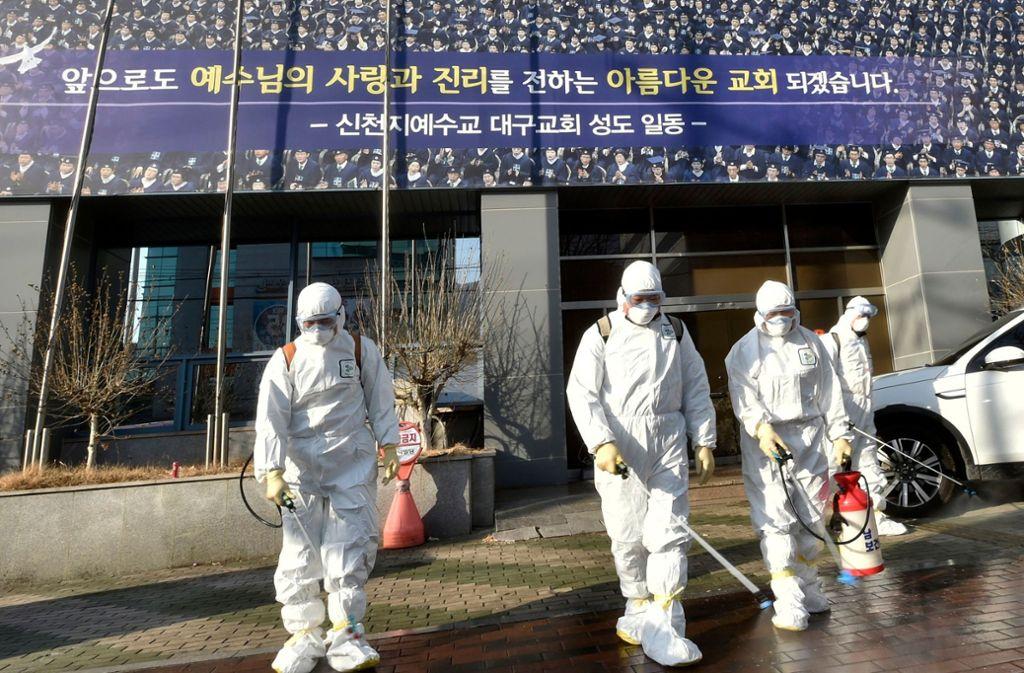 Vor der Shincheonji Church of Jesus in der südkoreanische Stadt Daegu versprühten Mitarbeiter der Gesundheitsbehörde Desinfektionsmittel. Foto: AFP
