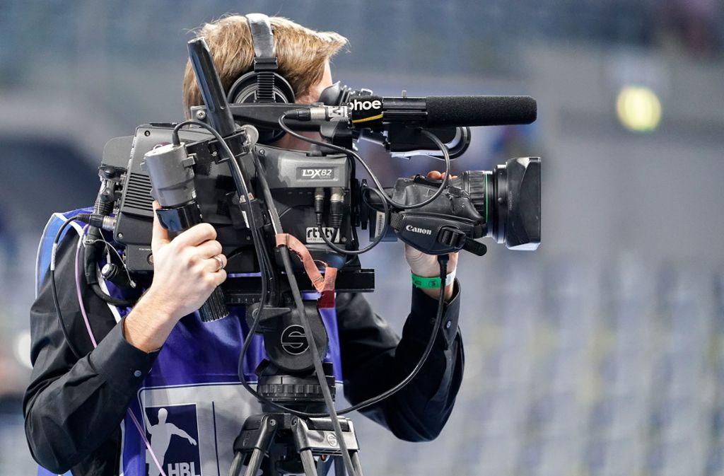 Ein Kameramann mit Kamera filmt ein Spiel in der Handball-Bundesliga. Foto: imago images/foto2press/Oliver Zimmermann via www.imago-images.de