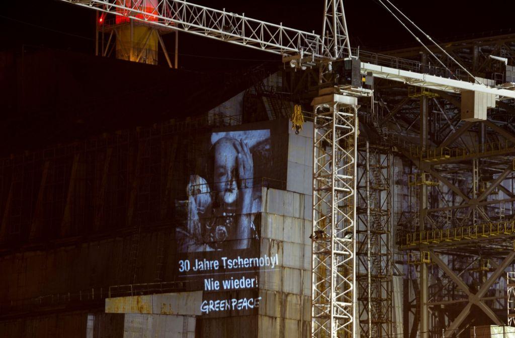 """Eine Projektion der Umweltschutzorganisation Greenpeace, das ein Foto von Robert Knoth und die Aufschrift """"30 Jahre Tschernobyl - Nie wieder"""" zeigt, auf den Außenmauern des ehemaligen Atomreaktors in Tschernobyl (Ukraine). (Archivfoto) Foto: dpa/Greenpeace"""