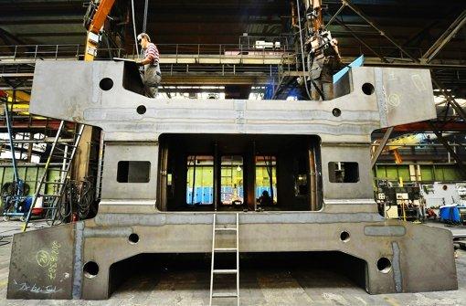 Mitarbeiter von Schuler in Erfurt bauen eine Großpresse zusammen. Foto: dpa
