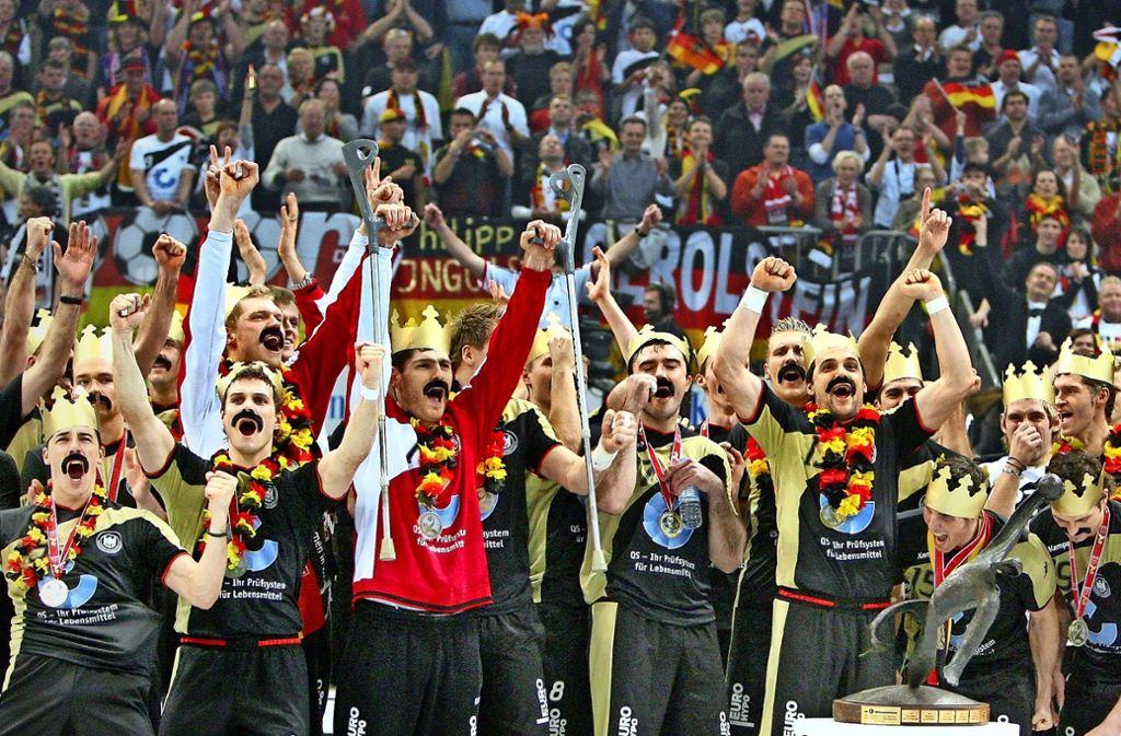Ekstase pur nach dem Titelgewinn bei der WM 2007: Michael Kraus (2. v. li.) und Johanns Bitter (hinter Kraus) feiern mit Heiner-Brand-Bärten und goldenen Pappkronen bei der Siegerehrung in Köln. Foto: dpa
